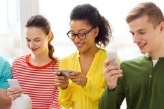 Drei lächelnde Studenten mit Smartphone in der Schule Stockfoto