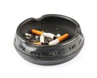 Drei löschten Zigaretten in einem schwarzen Aschenbecher Stockfotografie