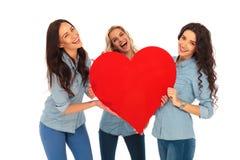 Drei lachende zufällige Frauen, die ein großes rotes Herz halten Stockfoto