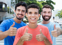 Drei lateinisch und kaukasische Freunde, die sich Daumen zeigen stockbild
