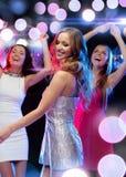 Drei lächelnde Frauen, die in den Verein tanzen Lizenzfreie Stockfotos