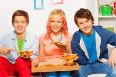 Drei lächelnde Freundgriff-Pizzastücke und essen Stockbilder