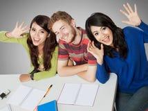 Drei lächelnde Studenten, die zusammen studieren Stockfotos