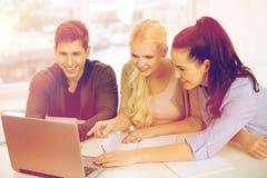 Drei lächelnde Studenten mit Laptop und Notizbüchern Stockbilder