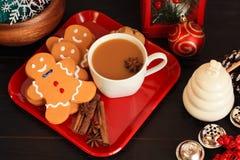 Drei Lebkuchenmannplätzchen mit Kaffee auf rotem Teller lizenzfreies stockbild