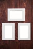 Drei leere Rahmen auf braunem hölzernem Schreibtisch Stockfotografie