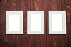 Drei leere Rahmen in der Mitte auf braunem hölzernem Schreibtisch Stockbilder