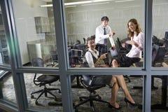 Drei Lehrer, die im BibliotheksComputerraum sich treffen Lizenzfreie Stockbilder