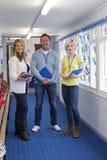 Drei Lehrer im Schulkorridor Stockfoto