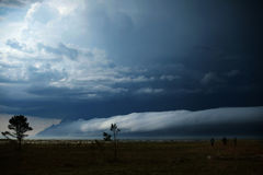 Drei Leute betrachten die auftauchenden Wolken über dem Meer während eines Sturms stockfotos