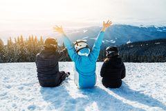 Drei Leute in den Skianzügen sitzen auf dem Schnee an der Spitze des Berges und untersuchen den Abstand stockbild