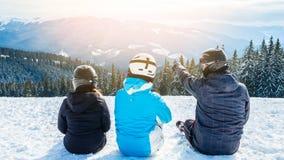 Drei Leute in den Skianzügen sitzen auf dem Schnee an der Spitze des Berges und untersuchen den Abstand lizenzfreies stockbild
