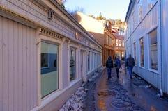Drei Leute in der Winterkleidung in einer schmalen Straße Lizenzfreies Stockbild