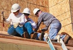 Drei Leute errichten Dach für Haus für Lebensraum für Menschlichkeit Stockfoto