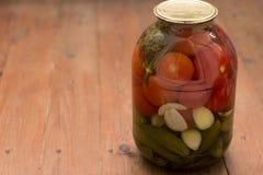 Drei-Liter Bank mit Gurken und Tomaten auf einem Holztisch lizenzfreies stockbild