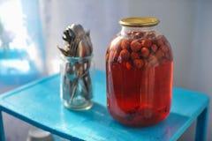 Drei-Liter-Glasgefäß mit dem Erdbeerkompott in Büchsen konserviert auf blauem Vorsprung Stockbilder