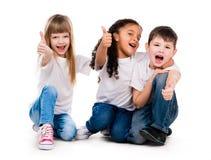 Drei lustige Kinder, die auf dem Boden mit den Daumen oben sitzen Stockfotos