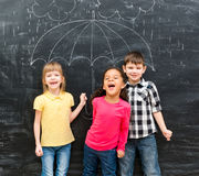 Drei lustige Kinder mit dem Regenschirm gezeichnet auf die Tafel Stockfoto