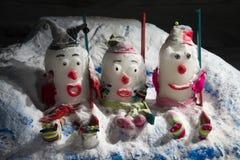 Drei lustige Schneemänner mit dem Strickmützesitzen lizenzfreies stockfoto