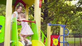 Drei Mädchen auf einem Spielkomplex auf dem Spielplatz stock footage
