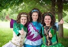 Drei Mädchen auf Iren tanzen die Kleider, die sich Daumen zeigen Stockbild