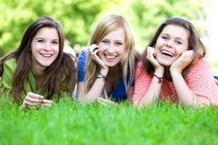 Drei Mädchen, die auf dem Gras liegen Stockfotografie