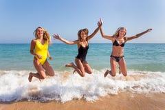 Drei Mädchen, die auf Strand nahe Meer springen lizenzfreie stockfotografie