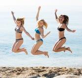 Drei Mädchen, die auf Strand springen stockbild