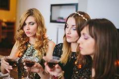Drei Mädchen, die ihre Getränke an einer Partei überprüfen Stockfotos