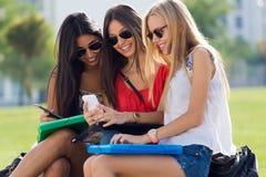 Drei Mädchen, die mit ihren Smartphones am Campus plaudern Stockfotografie
