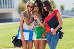 Drei Mädchen, die mit ihren Smartphones am Campus plaudern Stockfotos