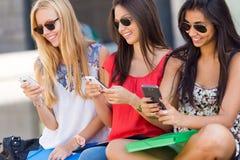 Drei Mädchen, die mit ihren Smartphones am Campus plaudern Stockfoto