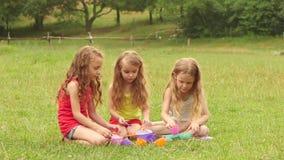 Drei Mädchen, die mit Spielwaren auf Natur spielen Langsame Bewegung stock video