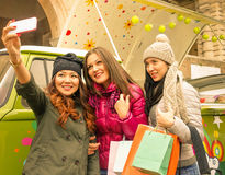 Drei Mädchen, die selfie in der Stadt nach dem Einkauf nehmen Stockfotos