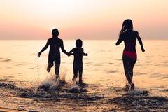 Drei Mädchen, die Spaß am Sonnenuntergangstrand - Freundschaftsfreiheit beac haben lizenzfreie stockfotos