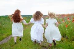 Drei Mädchen, die zusammen verbindende Hände laufen lassen Lizenzfreie Stockbilder