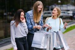 Drei Mädchen gehen mit Käufen vom Speicher lizenzfreie stockfotografie