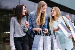 Drei Mädchen gehen mit Käufen vom Speicher lizenzfreie stockfotos