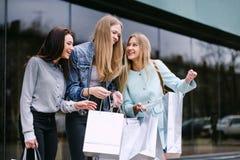 Drei Mädchen gehen mit Käufen vom Speicher stockbilder