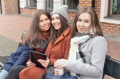 Drei Mädchen sitzen auf der Bank draußen Lizenzfreies Stockfoto