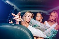 Drei Mädchen sitzen im Auto und schauen auf Karte Blondes Mädchen zeigt vorwärts Sie sprechen mit einander Stockfoto