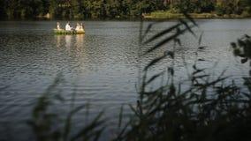 Drei Mädchen und ein Kerl im slawischen Nationalkostüm, das in ein Boot schwimmt Mädchen in den Kränzen in einem Boot Nationale T stock video footage