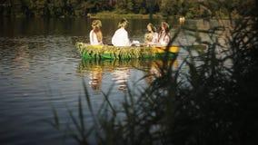 Drei Mädchen und ein Kerl im slawischen Nationalkostüm, das in ein Boot schwimmt Mädchen in den Kränzen in einem Boot Nationale T stock footage