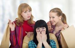 Drei Mädchenfreundinnen, die mit dem Einkaufen sich befassen stockbilder