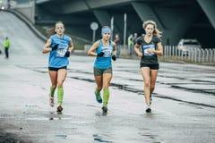 Drei Mädchenläufer laufen gelassen auf nassem Asphalt Stockbild