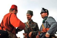 Drei Männer in den bunten historischen Kostümen, die miteinander sprechen Stockfoto