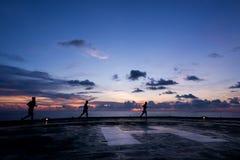 Drei Männer, die an laufen, heben oben Ölplattformhubschrauber-landeplatz Lizenzfreies Stockfoto