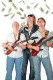 Drei Männer mit zwei Gitarren schauen auf fallendem Dollar Lizenzfreies Stockfoto