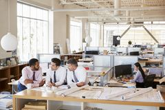 Drei männliche Architekten in der Diskussion in einem Bürogroßraum lizenzfreie stockfotografie