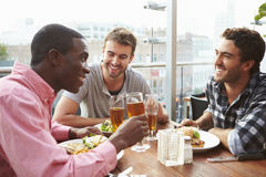 Drei männliche Freunde, die das Mittagessen am Dachspitzen-Restaurant genießen Stockfotografie